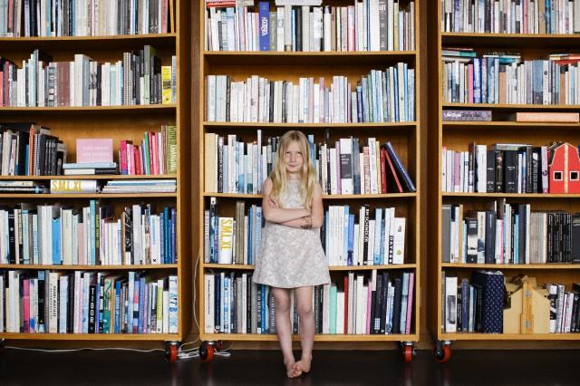 Girl (6-7) standing in front of bookshelf