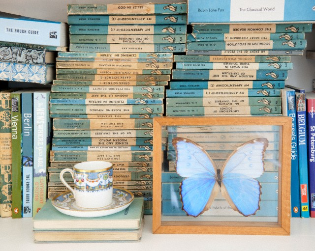 Interior detail of antique and vintage books and ornaments on a shelf in a Cotswolds country cottage