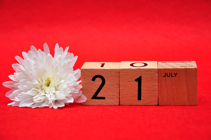 21 July on wooden blocks with a white daisy on a red background